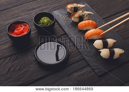 Eating sushi. Japanese food restaurant, unagi and salmon sushi on dark background. Taking piece with chopsticks. Closeup on black wood