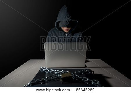Male Hacker behind laptop computer attacking another laptop computer with chains and lock Ransomeware cyber attack concept