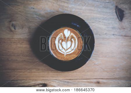 Top view image of hot piccolo latte coffee with latte art on vintage wooden table