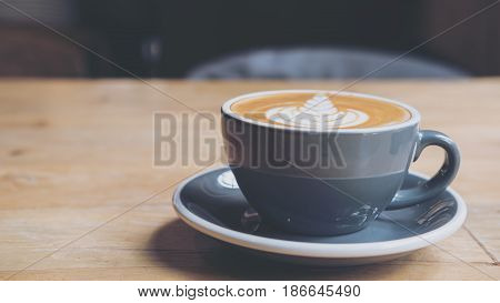 Closeup image of hot latte coffee with latte art on vintage wooden table
