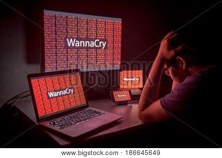 Young Asian male frustrated confused and headache by WannaCry ransomware attack on desktop screen notebook and smartphone cyber attack internet security concept