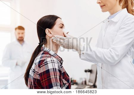 Doing rhino plastics. Nice cheerful positive doctor holding her patients face and putting a medical dressing on the nose while standing in front of her