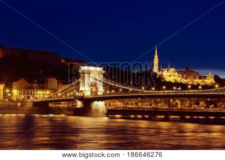 Beautiful night Budapest, the Chain bridge across the Danube river in lights with dark blue sky, Travel outdoor sightseeing european background.