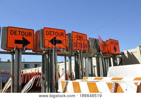 A series of DETOUR metal signs in a construction yard display the many driving directions involving a detour.