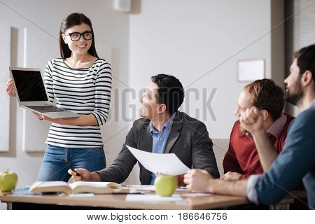 Believe me. Beautiful smiling brunette keeping laptop on both hands wearing glasses, looking at her coworkers
