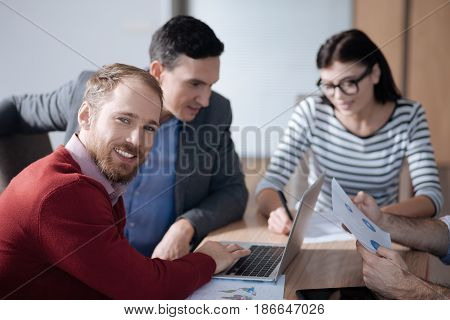 Look at me. Young attractive man wearing red cardigan putting fingers on keyboard while posing on camera