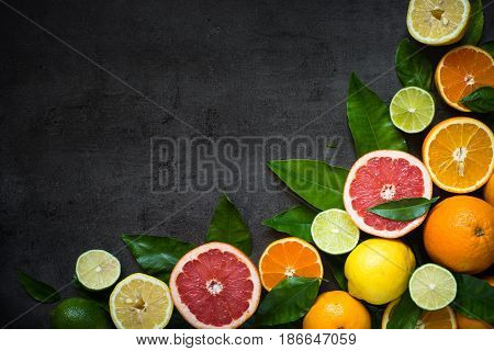 Fresh citrus fruit assortment. Whole and sliced citrus fruit on black slate table. Fruit food background. Healthy eating and diet.