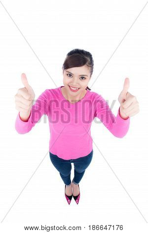 High angle perspective of a happy smiling young woman looking up at the camera giving a double thumbs up of success and approval isolated on white background.