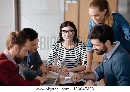 Work in groups. Group of office workers wearing casual clothes sitting at their places while thinking about project