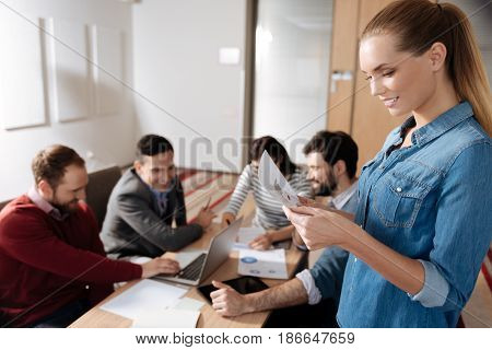 Present your ideas. Positive delighted blonde holding diagram in both hands expressing positivity while reading it