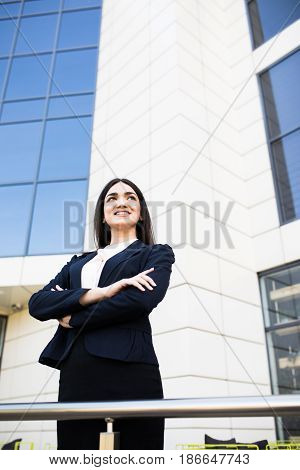 Beautiful Young Businesswoman With Crossed Hands In Front Of Skyscrapers Of The Modern Business Cent
