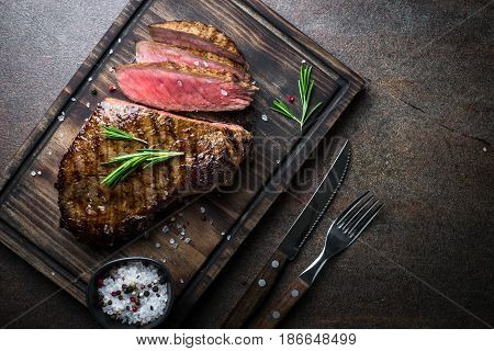 Fresh grilled meat. Grilled beef steak medium rare on wooden cutting board. Top view copy space.