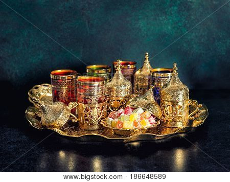 Tea table with golden dishes. Oriental hospitality. Ramadan kareem. Vintage style toned picture