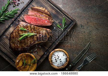 Fresh grilled meat. Grilled beef steak medium rare on wooden cutting board. Top view with copy space.