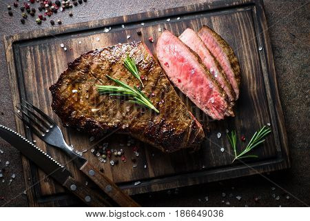 Fresh grilled meat. Grilled beef steak medium rare on wooden cutting board. Top view.