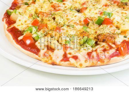 Homemade Hawaiian Pizza on white plate close up
