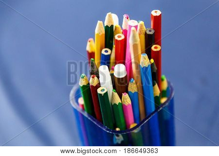 Color pencils and markers stand in a blue plastic container
