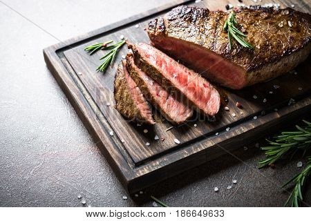 Grilled beef steak medium rare with herbs on wooden cutting board. Copy space.