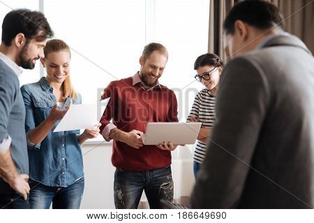 Be in time. Attractive bearded man wearing red cardigan keeping smile on his face while looking at screen of computer