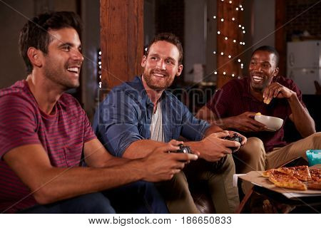 Three male friends playing video games looking at each other