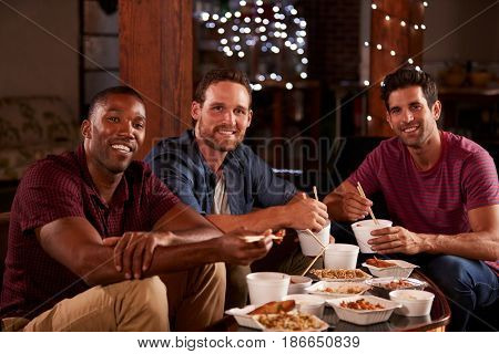 Three male friends eating a Chinese take-away look to camera