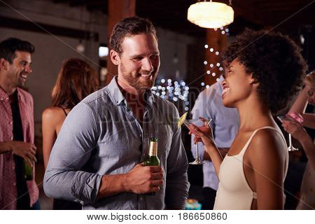 White man and mixed race woman talking at a party, side view