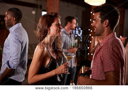 Young man and woman talking at a party, side view