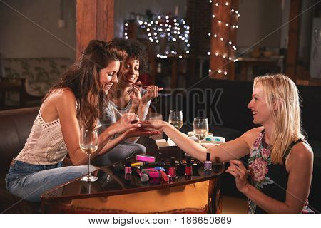 Female friends hanging out and doing their nails at home