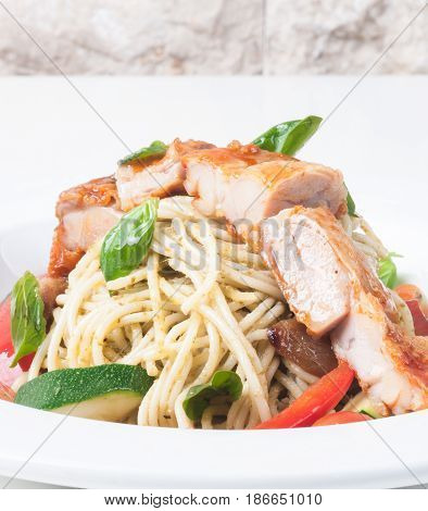 Spaghetti with roasted chicken on a white plate
