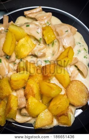 Mushroom Sauce And Potatoes On Black Plate