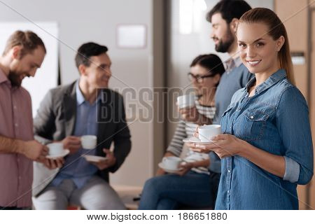 Time for coffee. Positive delighted office worker keeping smile on face wearing jeans shirt while looking straight at camera