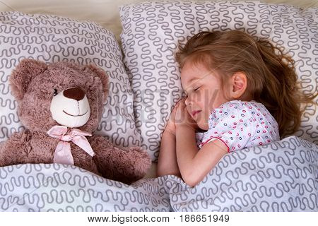 The little girl is sleeping with a teddy bear. Each on his pillow