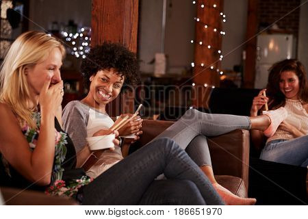 Friends share a joke and Chinese food at a girlâ??s night in