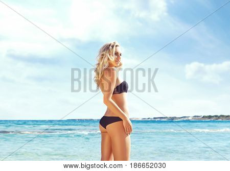 Beautiful woman in black bikini relaxing on a summer beach. Traveling, vacation, concept.