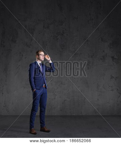 Businessman standing over dark wall background. Business, career job concept.