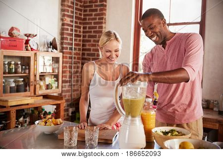 Happy mixed race couple making smoothies, using blender