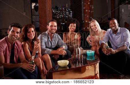 Group of friends at a house party sit looking to camera