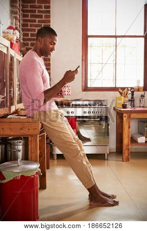 Young black man using smartphone in kitchen, full length