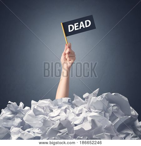 Female hand emerging from crumpled paper pile holding a black flag with dead written on it