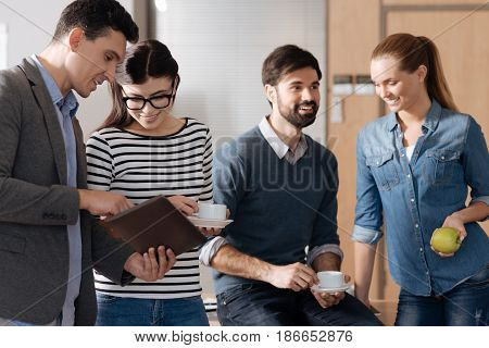 Young professionals. Positive delighted man holding tablet in hands bowing head while standing in semi position