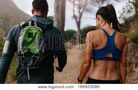 Fit Young Couple Walking On Mountain Trail