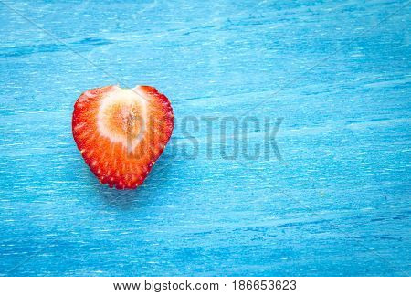 Sliced strawberries on a blue background. Macro photo