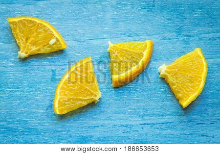 Pieces of orange on a blue wooden background