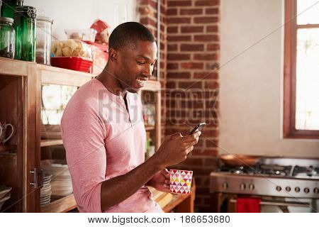 Young black man using smartphone in kitchen, close up
