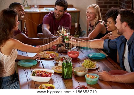 Six friends making a toast at a dinner party, elevated view