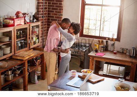 Mixed race couple embracing in kitchen, elevated view