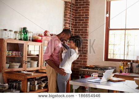 Mixed race couple embracing in kitchen