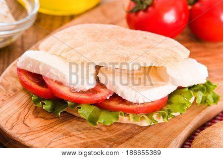 Puccia bread with mozzarella and tomato on cuttingboard.