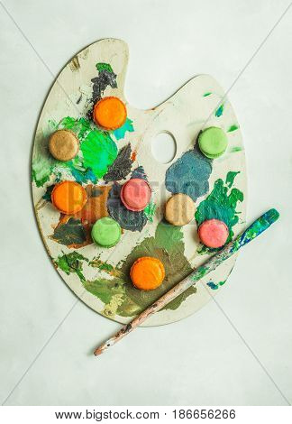 Colorful french macaroons placed on a stained artist pallate and used paint brush along side. Conceptual food photography.
