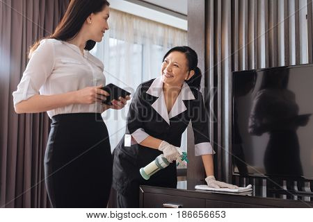 Hotel service. Joyful nice positive businesswoman standing near a hotel maid and talking to her while holding a tablet